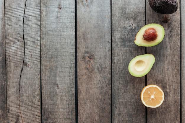 Gesundes esskonzept flach lag. mediterrane ernährung, holztisch mit avocadohälften, ganze avocado, avocadokern, zitronenhälfte. vegetarisches essen. gesundes lebensmittelkonzept. bio-lebensmittel