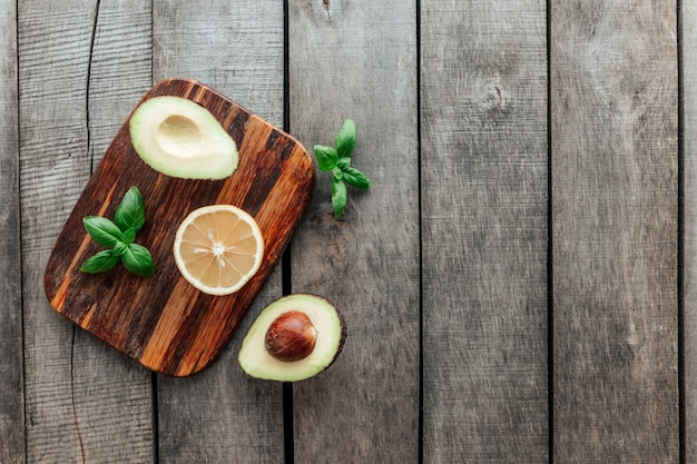 Gesundes esskonzept flach lag. mediterrane ernährung, schneidebrett mit avocadohälften, kern, basilikum und zitronenhälfte auf holztisch. vegetarisches essen. gesundes lebensmittelkonzept. bio-lebensmittel