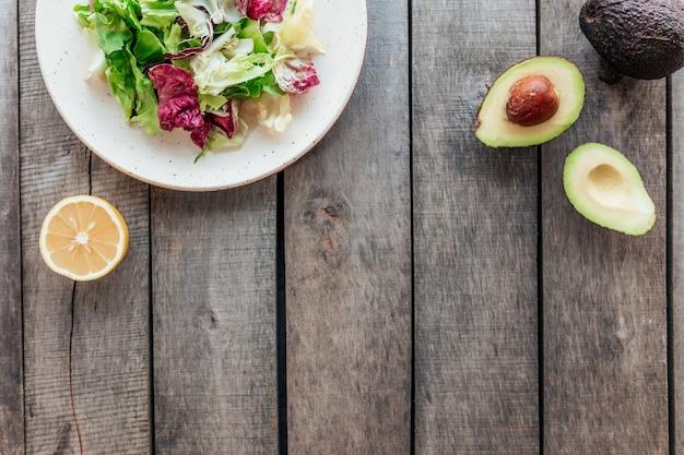 Gesundes esskonzept flach lag. mediterrane ernährung, teller mit frischen grünen salat-salatblättern, lila radicchio-blättern, avocado-hälften mit kern, ganze avocado, zitrone auf holztisch