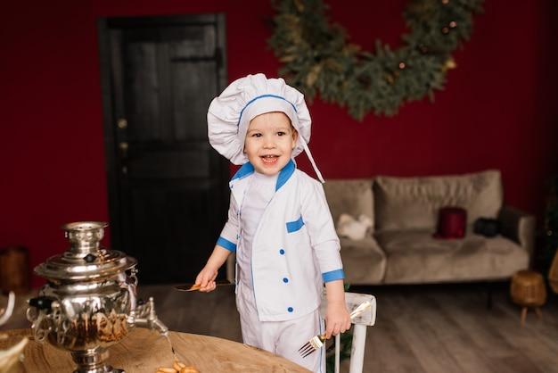 Gesundes esskonzept. glücklicher kleiner junge kocht in der küche an einem sonnigen sommertag. kleinkindbäcker auf einem picknick isst brot und bagels in einer weißen schürze und einem hut