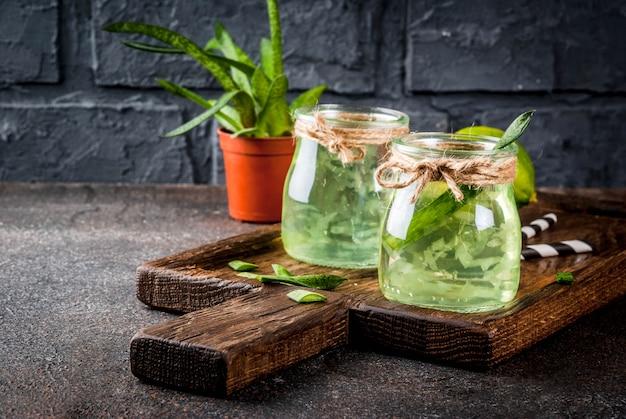 Gesundes exotisches detoxgetränk aloe vera oder kaktussaft mit kalk auf dunklem hintergrund