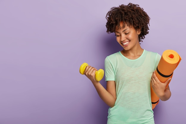 Gesundes fitness-mädchen hebt gewicht hantel, arbeitet, um bizeps zu haben, trägt gerolltes karemat