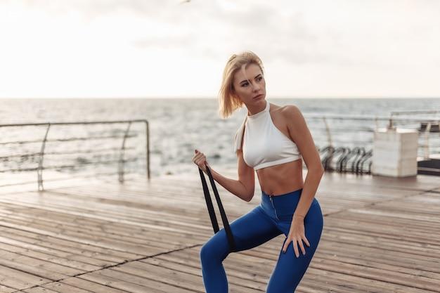 Gesundes frauentraining an der strandpromenade sportlerin in sportbekleidung, die übung mit fitness rubbe tut