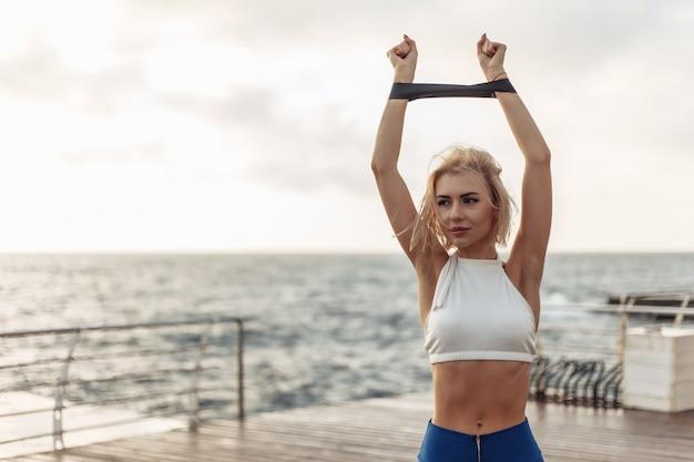Gesundes frauentraining an der strandpromenade sportlerin in sportbekleidung, die übung mit fitnessgummi tut
