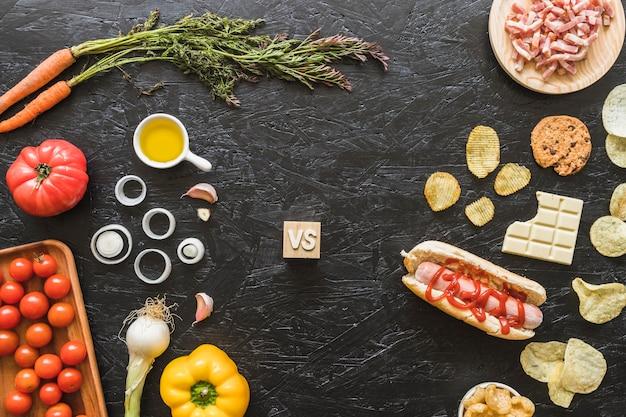 Gesundes frisches organisches gemüse gegen ungesunde fertigkost auf küchenarbeit
