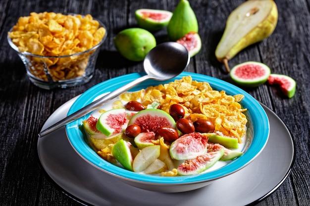 Gesundes frühstück am morgen: blaue schüssel mit naturjoghurt mit knusprigen cornflakes, feigen, birne serviert auf einer schwarzen holzoberfläche, draufsicht, nahaufnahme