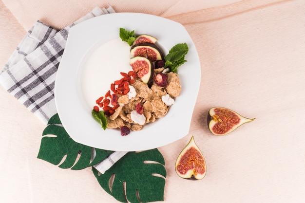 Gesundes frühstück auf teller mit gefälschten monstera-blättern; feigenscheiben und küchenserviette