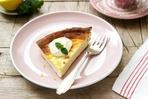 Gesundes frühstück aus weichem hüttenkäse-auflauf mit haferflocken und zitronenschale, serviert mit saurer sahne und minze.