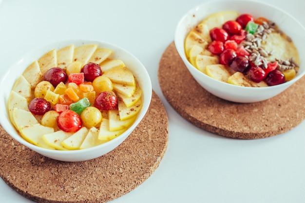 Gesundes frühstück. brei mit kirsche, apfel und kandierten früchten