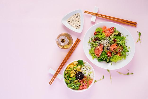 Gesundes frühstück. buddha-schale mit reis, mango, avocado und lachs und frischem salat mit tomaten, avocado, rucola, samen, lachs. gesundes lebensmittelkonzept. draufsicht. flach liegen