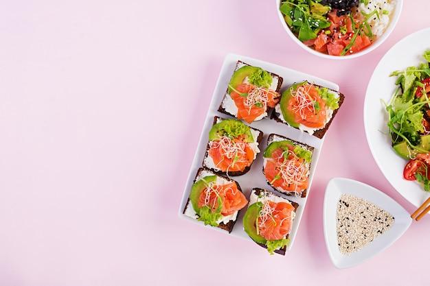Gesundes frühstück. buddha-schale mit reis, mango, avocado und lachs und frischem salat mit tomaten, avocado, rucola, samen, lachs-lachs-sandwich mit avocado, milchkäse und mikrogrün. healt