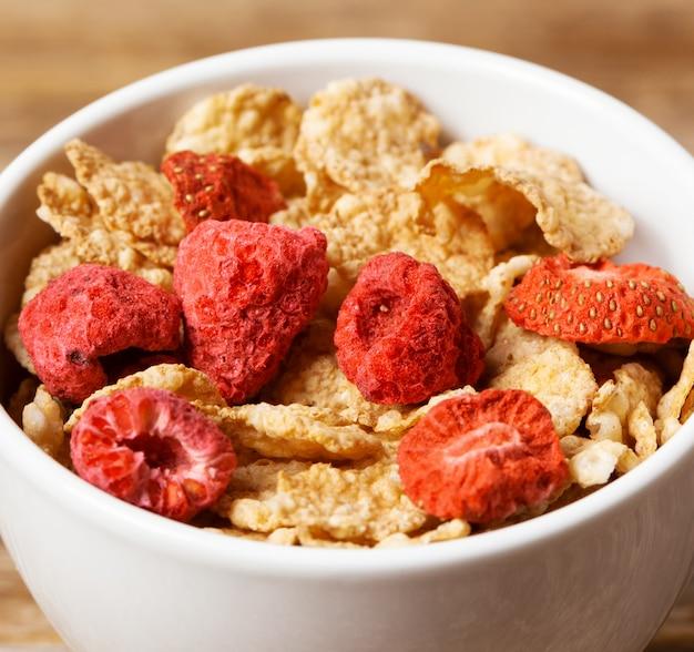 Gesundes frühstück cornflakes und erdbeeren mit milch
