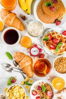 Gesundes frühstück, das konzept, verschiedenes morgenlebensmittel - pfannkuchen, waffeln, hörnchenhafermehlsandwich und granola mit joghurt, frucht, beeren, kaffee, tee, orangensaft, weißer hintergrund isst
