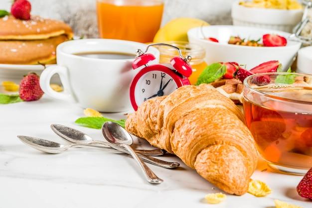 Gesundes frühstück, das konzept, verschiedenes morgenlebensmittel - pfannkuchen, waffeln, hörnchenhafermehlsandwich und granola mit jogurt, frucht, beeren, kaffee, tee, orangensaft isst
