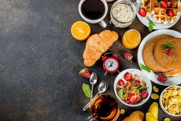 Gesundes frühstück, das verschiedenes morgenlebensmittel des konzeptes - pfannkuchenwaffelhörnchen-hafermehlsandwich und -granola mit dunklem rostigem hintergrund des jogurtfruchtbeerenkaffee-tee-orangensafts isst