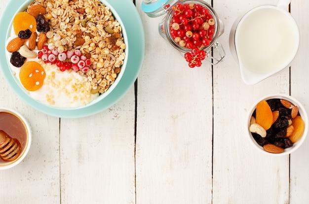 Gesundes frühstück der müslischale mit getrockneten früchten, nüssen und frischen roten johannisbeeren auf weißem holz