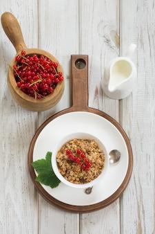 Gesundes frühstück des sommers des granolas, muesli mit milchkrug mit rote johannisbeerdekor auf hellem brett. ansicht von oben.