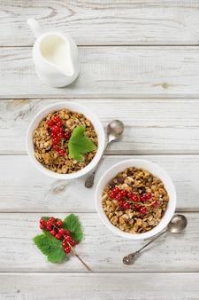 Gesundes frühstück des sommers für zweipersonengranola, müsli mit milchkrug mit dekor der roten johannisbeere