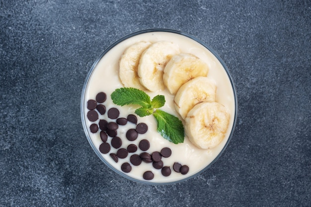 Gesundes frühstück, dessert mit milchjoghurtbanane und schokolade auf einem teller. dunkler konkreter hintergrund. draufsicht, kopierraum.