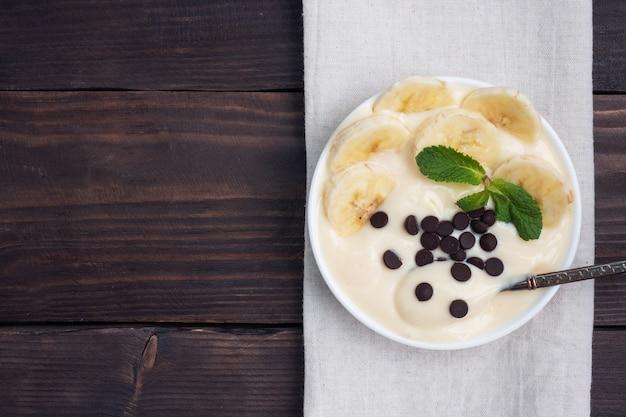 Gesundes frühstück, dessert mit milchjoghurtbanane und schokolade auf einem teller. dunkles holz. draufsicht, kopierraum.