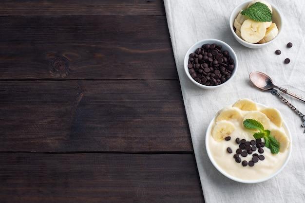 Gesundes frühstück, dessert mit milchjoghurtbanane und schokolade auf einem teller. dunkles holz. draufsicht