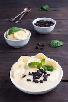 Gesundes frühstück, dessert mit milchjoghurtbanane und schokolade auf einem teller. dunkles holz.