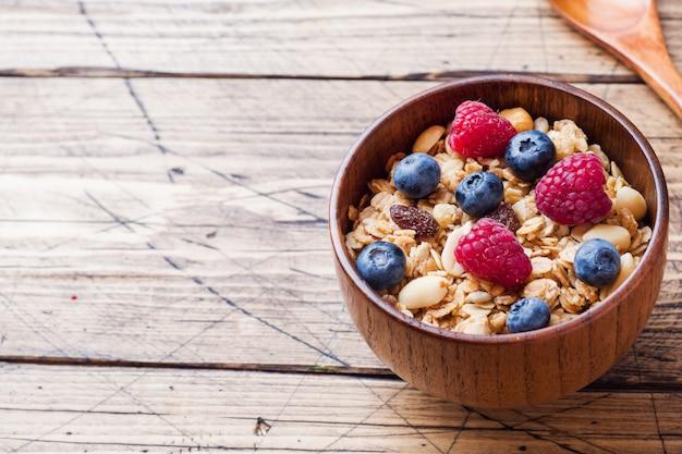 Gesundes frühstück. frisches müsli, müsli mit joghurt und beeren auf holzoberfläche