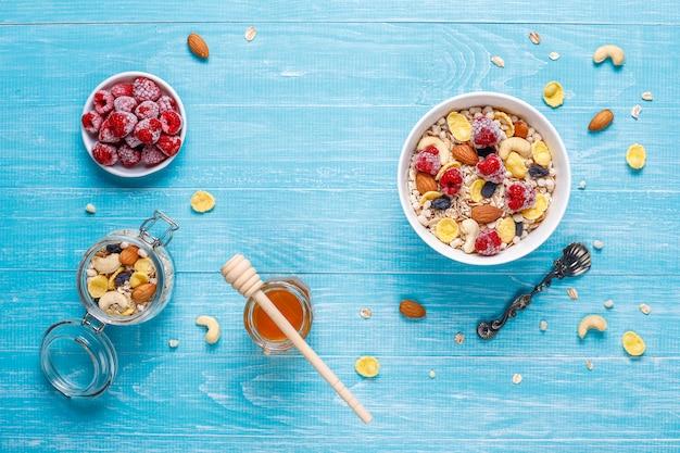 Gesundes frühstück. frisches müsli, müsli mit nüssen und gefrorenen beeren. draufsicht. speicherplatz kopieren.