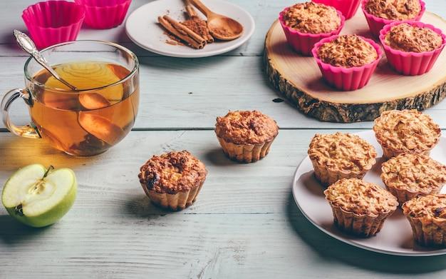 Gesundes frühstück. gekochte haferflockenmuffins mit apfel und tasse grünem tee über hellem holztisch.