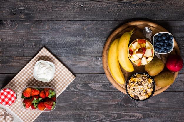 Gesundes frühstück, getreide mit joghurt, erdbeeren, blaubeere, apfel, banane, auf rustikalem hölzernem. ansicht von oben