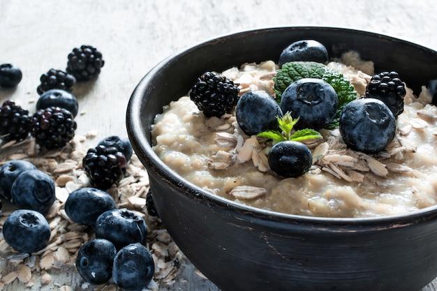 Gesundes frühstück. haferbrei mit reifen blaubeeren und brombeeren