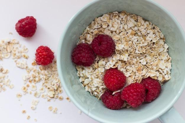 Gesundes frühstück haferbrei und fruchtbeeren auf einem weißen hintergrund