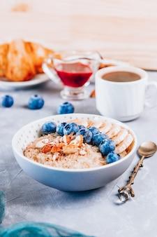 Gesundes frühstück - haferflocken, croissant und kaffee auf einem tisch