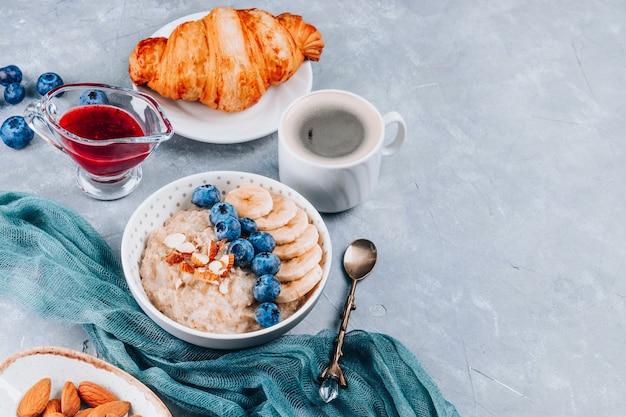 Gesundes frühstück - haferflocken, croissants und kaffee