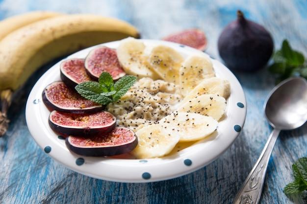 Gesundes frühstück: haferflocken mit frischen feigen, bananen, kokosmilch und chiasamen
