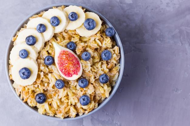 Gesundes frühstück. haferflocken mit heidelbeeren, bananen und feigen. haferflocken mit früchten und beeren in einer schüssel