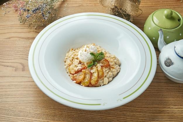 Gesundes frühstück - haferflocken mit karamellisierter banane und pochiertem ei, mandeln in einem weißen teller.
