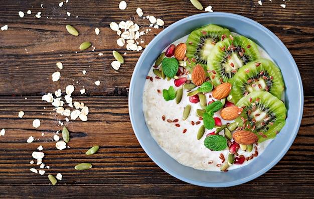 Gesundes frühstück. haferflocken mit kiwi, granatapfel, leinsamen und nüssen. detox-menü top vi