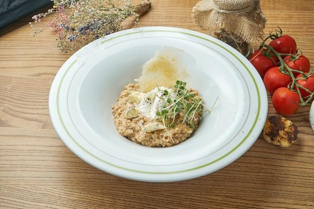 Gesundes frühstück - haferflocken mit pochiertem ei, blauschimmelkäse und mikrogrün in einem weißen teller.