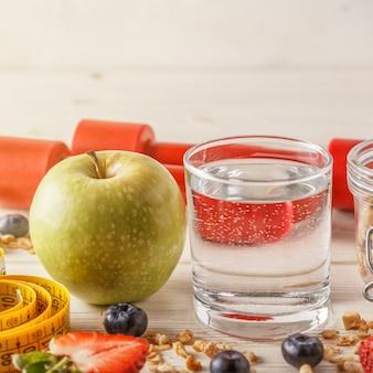 Gesundes frühstück, hanteln und maßband auf holzrücken