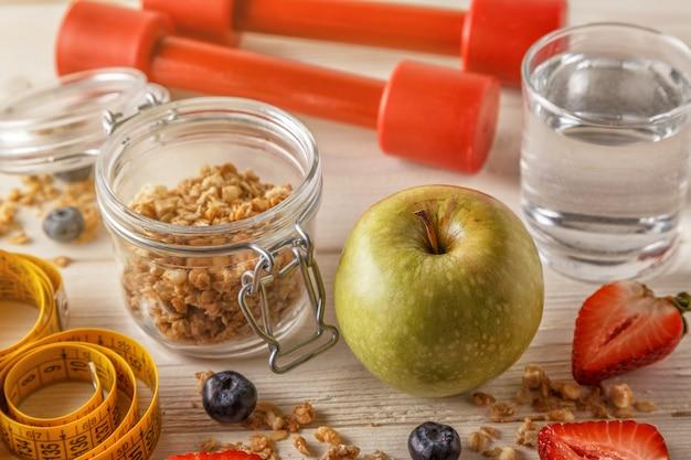 Gesundes frühstück, hanteln und maßband auf holztisch.