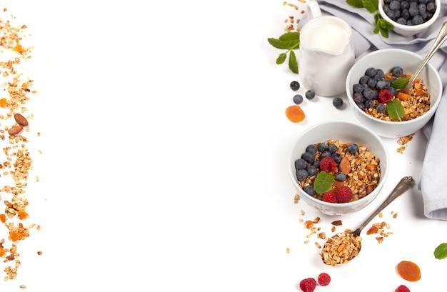 Gesundes frühstück - hausgemachtes müsli, honig, milch und beeren