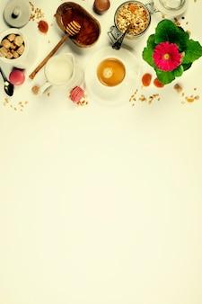 Gesundes frühstück - hausgemachtes müsli, honig und milch auf gelbem tischhintergrund mit copyspace