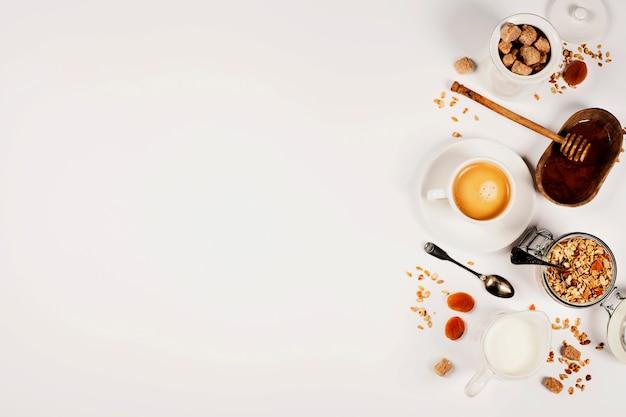 Gesundes frühstück - hausgemachtes müsli, honig und milch auf weißem tischhintergrund mit copyspace