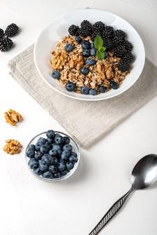 Gesundes frühstück. hausgemachtes müsli, müsli, müsli mit brombeeren, blaubeeren, nüssen, honig und minze in einer weißen schüssel