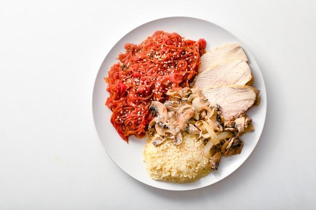 Gesundes frühstück. hühnerfilet, couscous, eintopf von gemüse und pilzen auf weißem hintergrund, draufsicht.