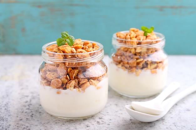 Gesundes frühstück: joghurt mit müsli in gläsern
