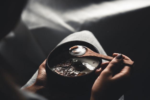 Gesundes frühstück. kokosnussschale in den händen eines mädchens mit joghurt und feigen. gesundes essen. veganismus.