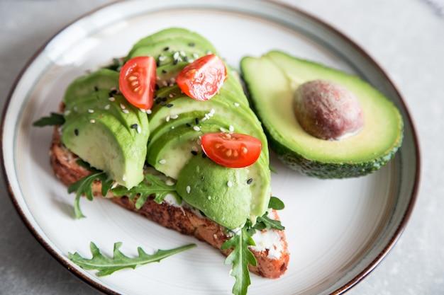 Gesundes frühstück mit avocado und köstlichem vollkornbrot. geschnittene avocado auf toastbrot mit gewürzen. mexikanische küche