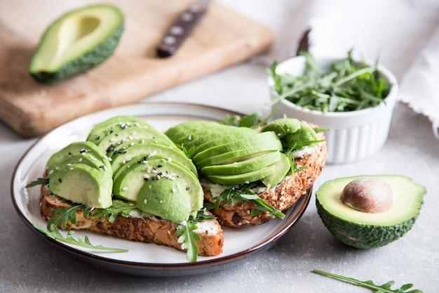 Gesundes frühstück mit avocado und köstlichem vollweizentoast. geschnittene avocado auf toastbrot mit gewürzen.